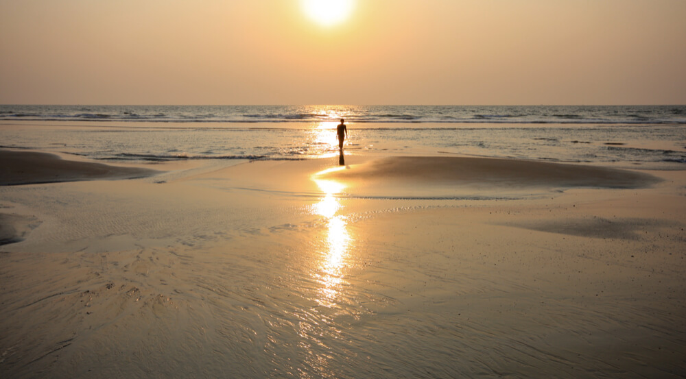 Glowing sunset on golden sands at varca beach Goa