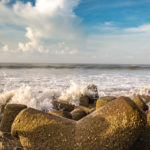 Sea waves splashing against the beach rocks at Digha beach, West Bengal, India.