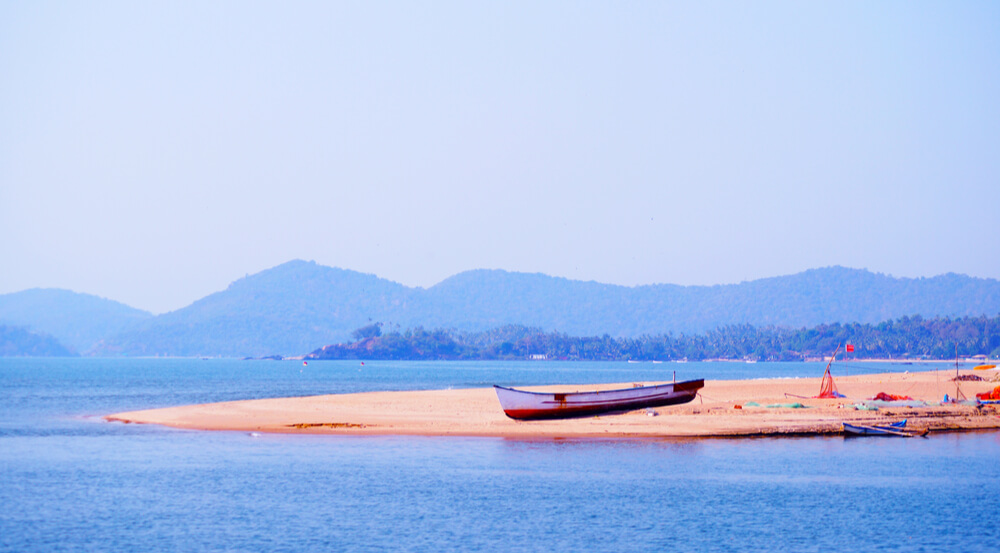 Lonely fisherman boat on the coast near Palolem beach. Talpona river. Mountain on the background.