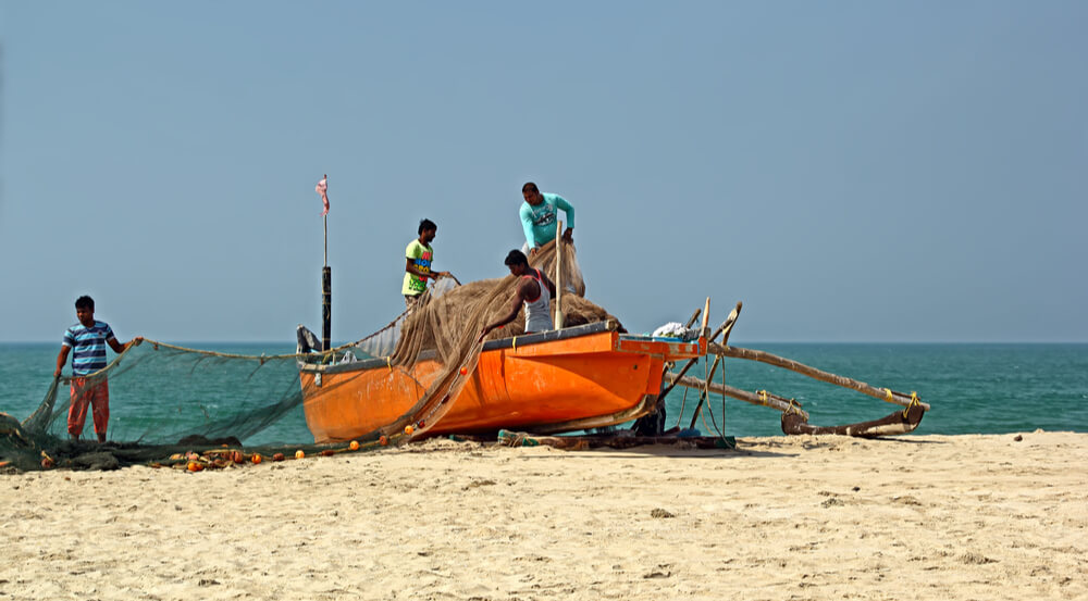 Fishermen load the boat with large net in preparation of fishing trip to the deep sea at Velsao Beach in Goa, India