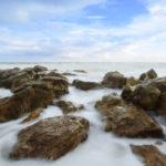 The beautiful silky smooth water waves and rocks at Yarada Beach, Visakhapatnam, India