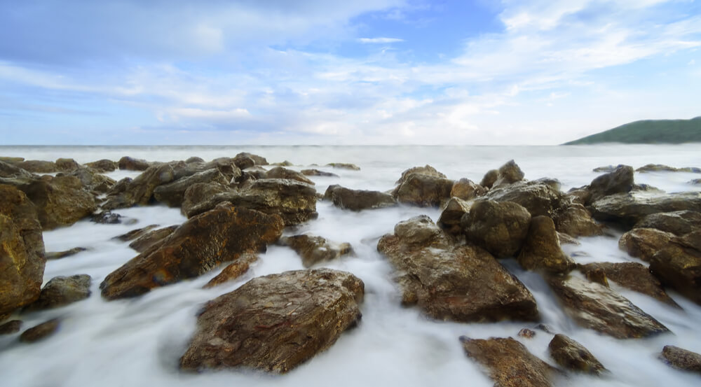 The beautiful silky smooth water waves and rocks at Yarada Beach, Visakhapatnam, India